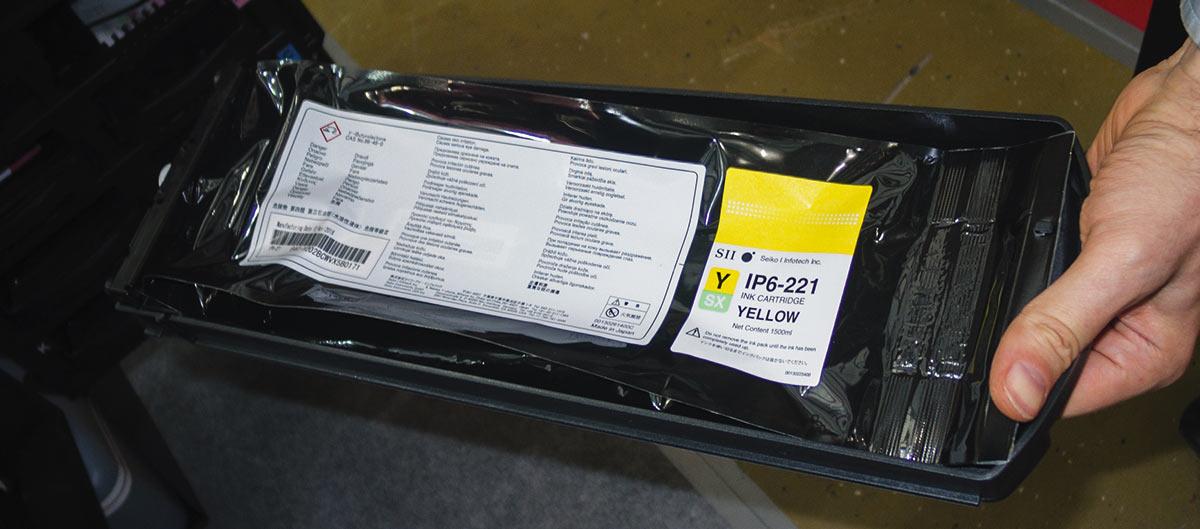 Пакет с желтыми чернилами, установленный в пластиковый поддон